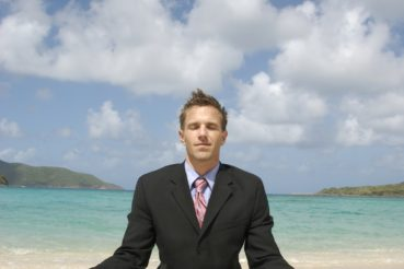 man-doing-yoga-in-business-suit-on-beach